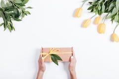 拿着有黄色丝带的女性手礼物盒在桌ne 免版税库存图片