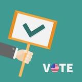 拿着有绿色壁虱校验标志的商人手纸空白的标志板材 投票文本徽章按钮美国国旗总统electio 库存图片