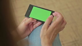 拿着有绿色屏幕显示和接触的俏丽的妇女巧妙的电话 影视素材