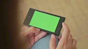拿着有绿色屏幕显示的俏丽的妇女手中巧妙的电话 股票录像