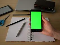 拿着有绿色屏幕的女性手一个智能手机 库存照片