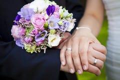 拿着有紫色花束的手新婚佳偶 库存照片
