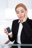 拿着有破裂的屏幕的女实业家智能手机 库存图片