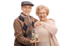 拿着有年长妇女的年长人金钱瓶子投入硬币 免版税库存图片