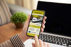 拿着有app旅馆预定的女性手电话在屏幕上 库存图片