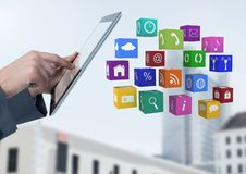 拿着有apps的商人片剂在大厦前面 免版税库存照片