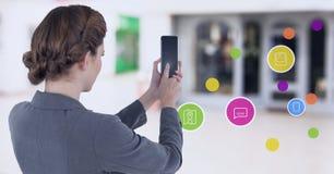 拿着有apps的女实业家手机在商城 免版税库存图片