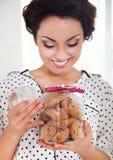 拿着有coockies的愉快的妇女瓶子在她的厨房里 库存图片