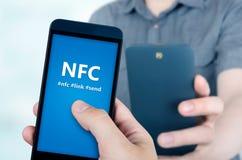 拿着有NFC技术的手智能手机 免版税库存图片