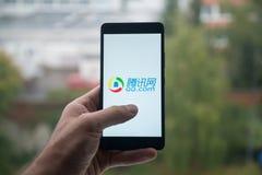 拿着有QQ的人智能手机 有手指的com在屏幕上 免版税库存图片