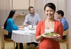 拿着服务妇女的开胃菜朋友 免版税库存图片
