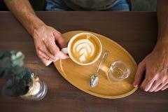 拿着服务的咖啡热奶咖啡和一杯在一个木盘子的水的一个人 在视图之上 免版税库存照片