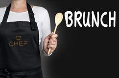 拿着木匙子背景的早午餐厨师 免版税库存图片