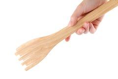 拿着木厨房钳子的手 免版税库存图片