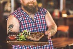 拿着木盘子的快乐的肥胖男性反对酒吧柜台 库存图片