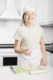 拿着未加工的新月形面包的微笑的男孩 库存图片