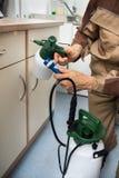 拿着杀虫剂喷雾器的害虫控制工作者 库存照片