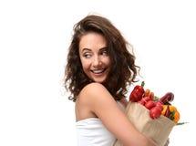 拿着杂货纸购物袋的少妇有很多新鲜蔬菜 饮食健康吃概念 库存图片