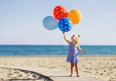 拿着束五颜六色的气球的愉快的小女孩在 免版税库存图片