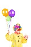 拿着束气球和玉米花箱子的服装的男性小丑 免版税库存照片