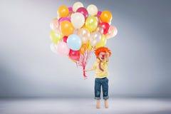 拿着束气球的小跳跃的男孩 免版税库存照片