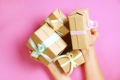 拿着束礼物的少妇包裹在手工制造空白的工艺纸缎带包装,缎弓 女性手,简单的giftbox, w 免版税图库摄影