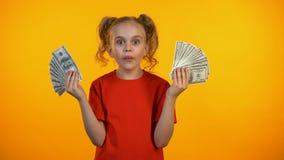 拿着束美元现金的惊奇的逗人喜爱的女孩,第一收入,银行业务 股票录像