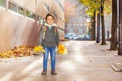 拿着束黄色叶子的愉快的男小学生 免版税库存图片