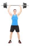 拿着杠铃的男性举重运动员 库存图片
