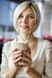 拿着杯与奶油的热巧克力的妇女在咖啡馆 库存照片