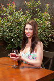 拿着杯在大阳台的酒的俏丽的妇女 库存图片