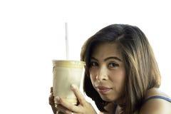 拿着杯在白色背景的冰冻咖啡的亚裔妇女与裁减路线 免版税库存图片
