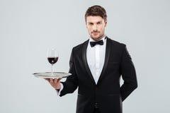 拿着杯在盘子的红葡萄酒的无尾礼服的侍者 免版税图库摄影