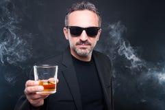 拿着杯威士忌酒的专属人 免版税库存照片