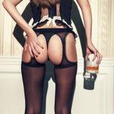 拿着杯威士忌酒的女用贴身内衣裤的肉欲的深色的妇女 免版税库存图片