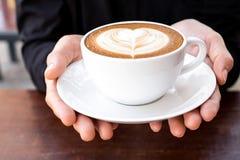 拿着杯子与心形的泡沫艺术的热的咖啡拿铁的手 库存照片