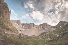 拿着杯子和放松在与湖的高山谷的远足者 夏天冒险和探险在阿尔卑斯 剧烈的天空,被定调子的imag 免版税库存照片