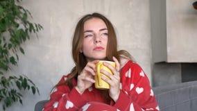 拿着杯子和看照相机的体贴的姜妇女,在家坐沙发,严肃和沉思 影视素材