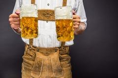 拿着杯子啤酒的传统巴法力亚衣裳的人 免版税库存照片