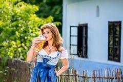 拿着杯子啤酒的传统巴法力亚礼服的妇女 免版税库存图片