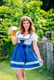 拿着杯子啤酒的传统巴法力亚礼服的妇女 免版税库存照片
