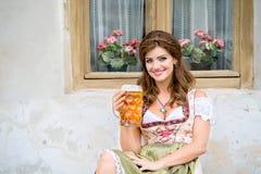 拿着杯子啤酒的传统巴法力亚礼服的妇女 库存照片