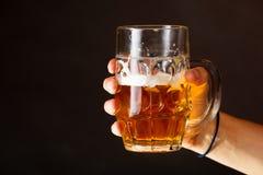 拿着杯子啤酒的男性手 库存照片