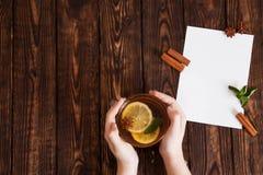 拿着杯子在桌的茶的手 免版税库存照片