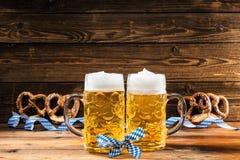拿着杯子巴法力亚啤酒慕尼黑啤酒节的手 免版税库存照片