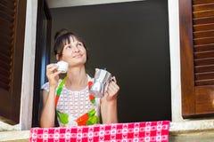 拿着杯子新近地煮的咖啡和意大利moka罐的中年妇女画象坐在开窗口附近与 图库摄影