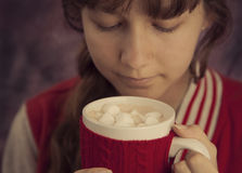 拿着杯子热巧克力的女孩用蛋白软糖 库存照片