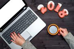 拿着杯子热的咖啡和键入在有空白的白色屏幕的,拷贝空间开放膝上型计算机键盘的妇女手顶视图 免版税图库摄影