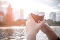 拿着杯子热的咖啡的手 库存照片