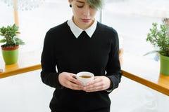 拿着杯子热的饮料的咖啡上瘾者女孩 库存照片